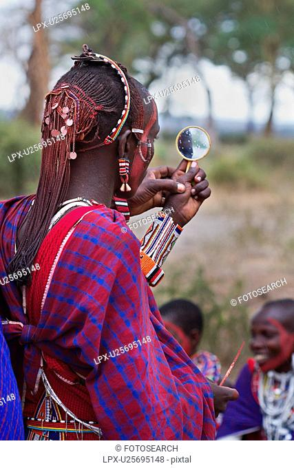 Close up side back view of young Masai warrior moran, with long braided hair, wearing traditional red shuka and beaded jewellery, with red facial paint