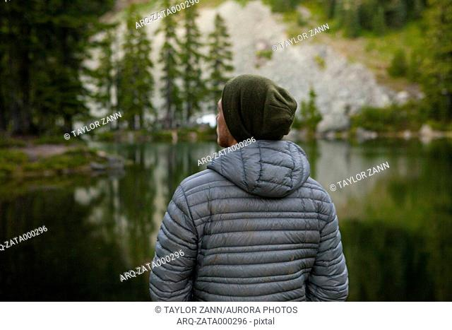 Rear view of man in knit hat and jacket by lake, Snoqualmie, Washington State, USA