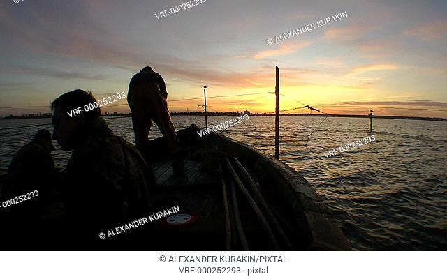 Fishing boat at sunrise in fixed nets. Black Sea. Ukraine