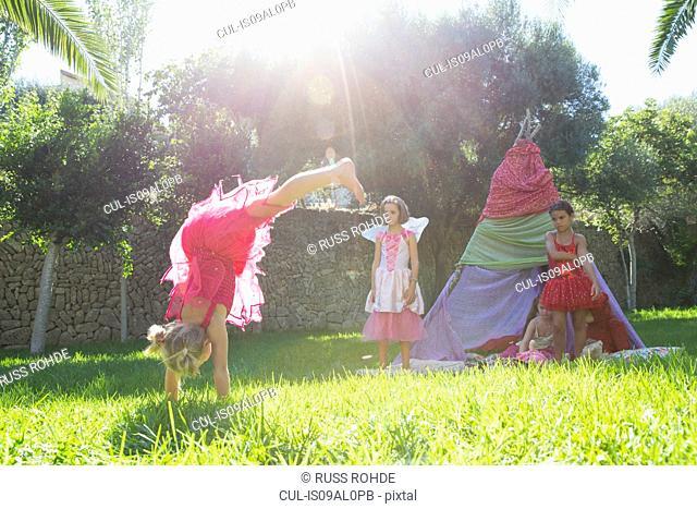 Girls watching friend in fairy costume doing handstand in garden