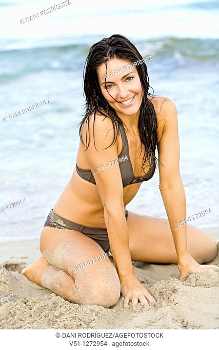 Portrait of a sensual brunette woman at the beach smiling at camera