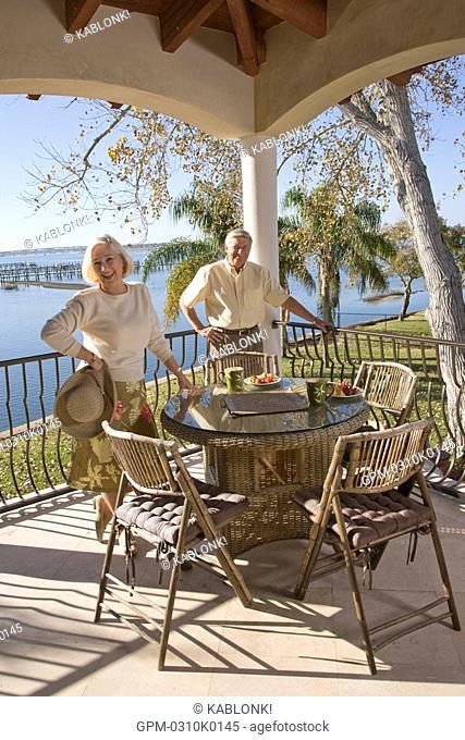 Portrait of senior couple relaxing on veranda of house