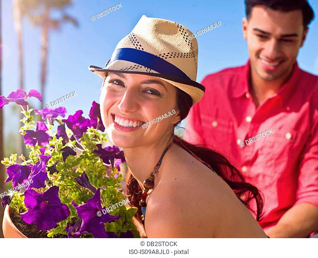 Young woman wearing sun hat and holding purple flowers, portrait