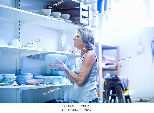 Senior woman in pottery workshop, placing bowl on shelf