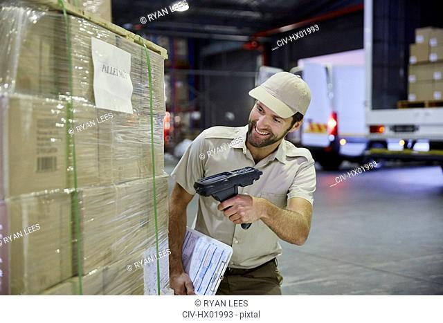 Truck driver worker scanning pallet of cardboard boxes at distribution warehouse loading dock