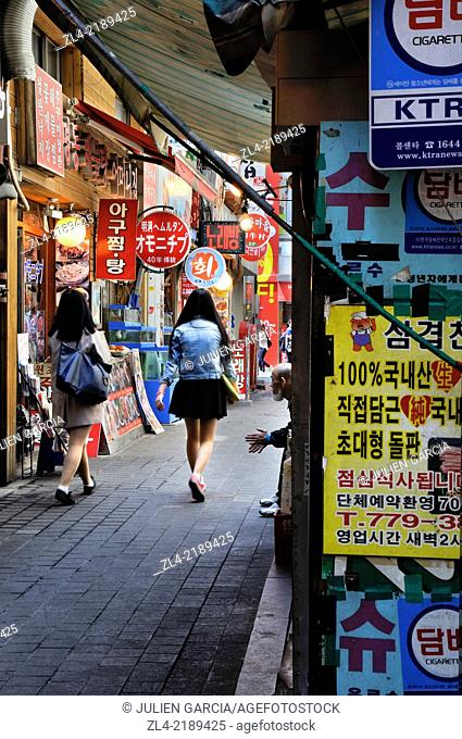 Woman in a small street in the city center in Myeongdong district. South Korea, Seoul