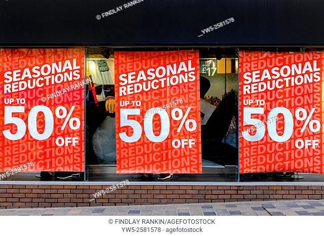 Sale posters in a shop window, Glasgow, Scotland, UK