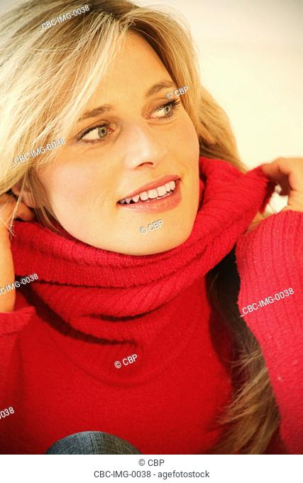 Portrait of Young Woman, Pulling Sweater over Face
