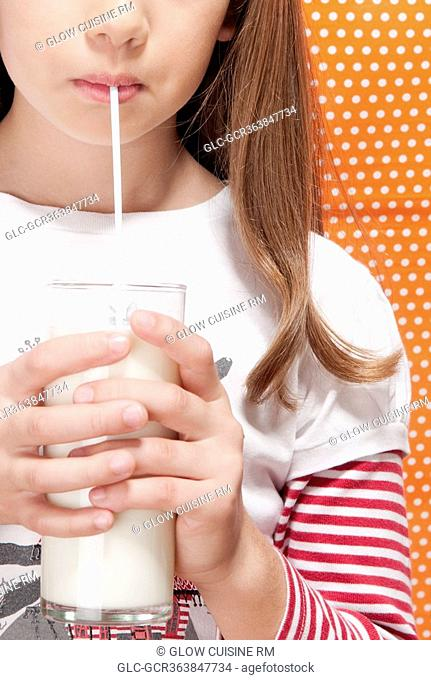 Girl drinking milk with a straw