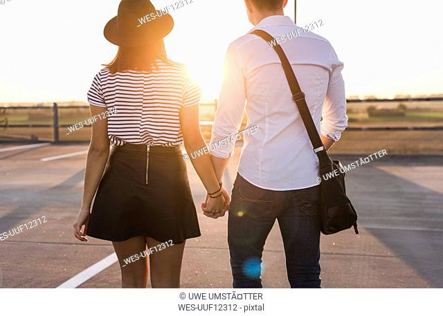 Young couple hand in hand on parking level at sunset