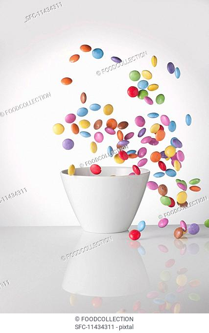 Colourful chocolate beans are flying around a bowl