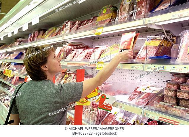 Woman at the cold cuts shelves in a supermarket