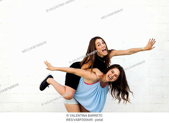 Laughing woman giving her best friend a piggyback ride in front of white wall