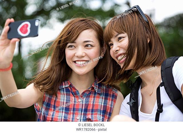 Two women, friends, taking a selfie in the park
