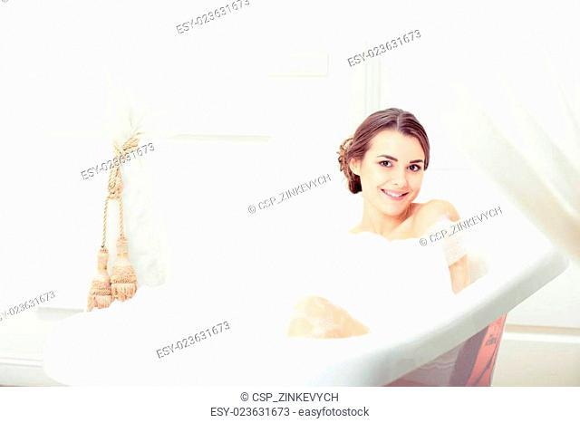 Beautiful young woman taking a bath
