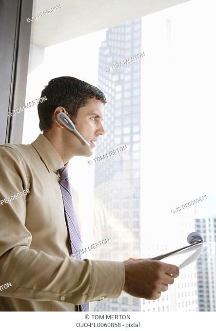 Businessman in corridor on earpiece by large window
