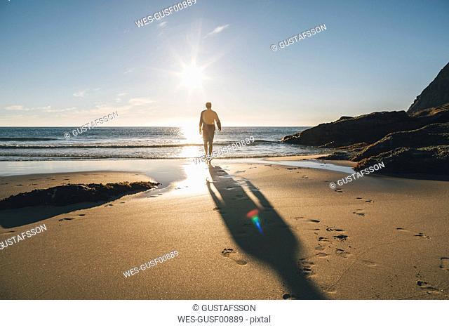 Norway, Lofoten, Moskenesoy, Man walking into the sun at Kvalvika Beach