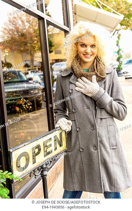 A 22 year old blond woman wearing winter clothes in a city environment