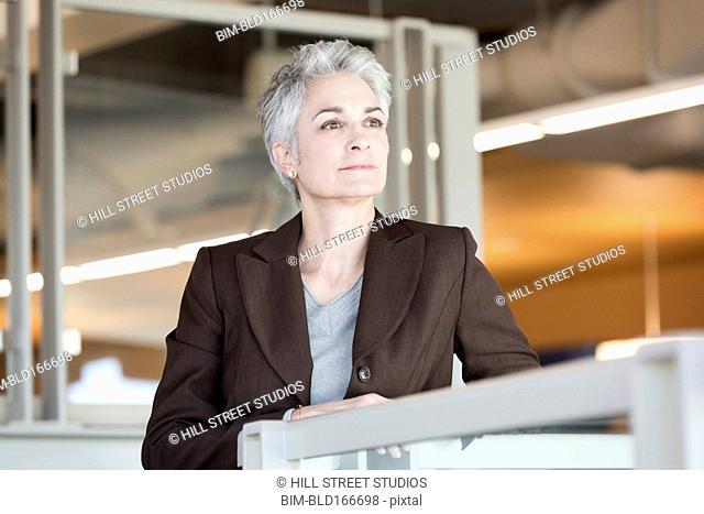 Caucasian businesswoman leaning on banister