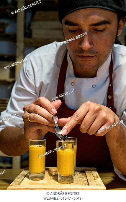 Chef putting caviar in a glass with sea urchin cream