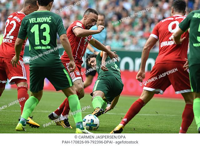 Bremen's Thomas Delaney (M) and Franck Ribery (3-L) of Munich vie for the ball during the Bundesliga soccer match between Werder Bremen and Bayern Munich at the...