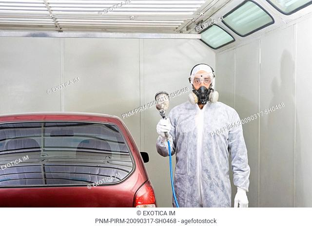 Auto mechanic holding a paint spray gun in a garage