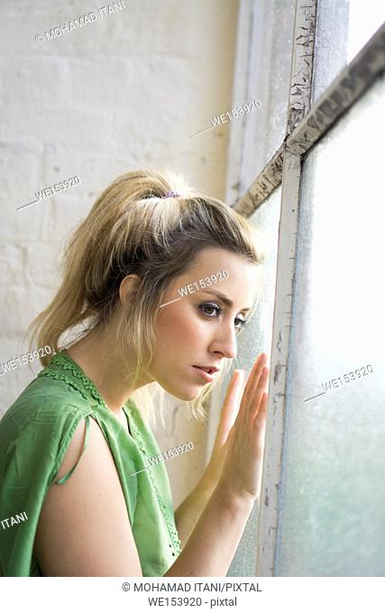 Worried young woman looking out of the window