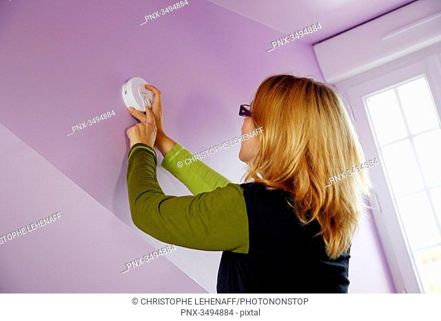 France, around Paris, 42 year old woman installing and testing a smoke detector