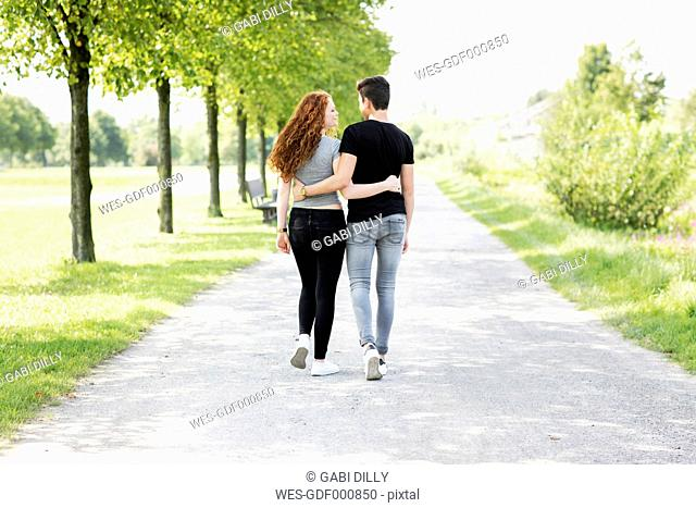 Teenage couple in love walking arm in arm