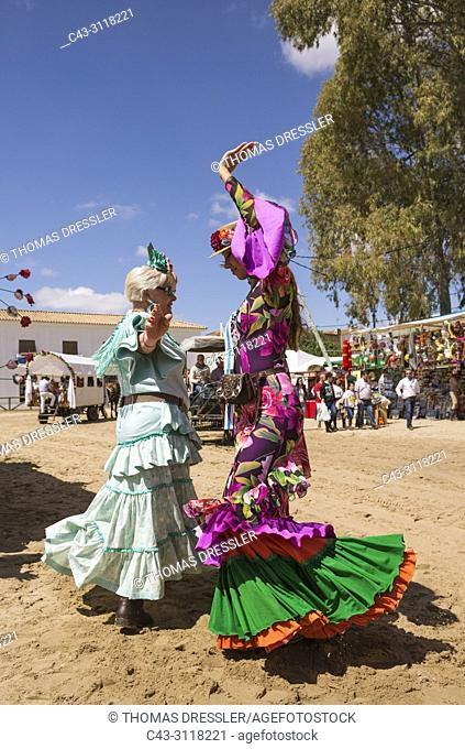 During the annual Pentecost pilgrimage of El Rocio the women wear beautifully coloured gypsy dresses and readily dance the Sevillana