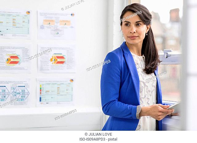 Businesswoman holding digital tablet and looking away in office