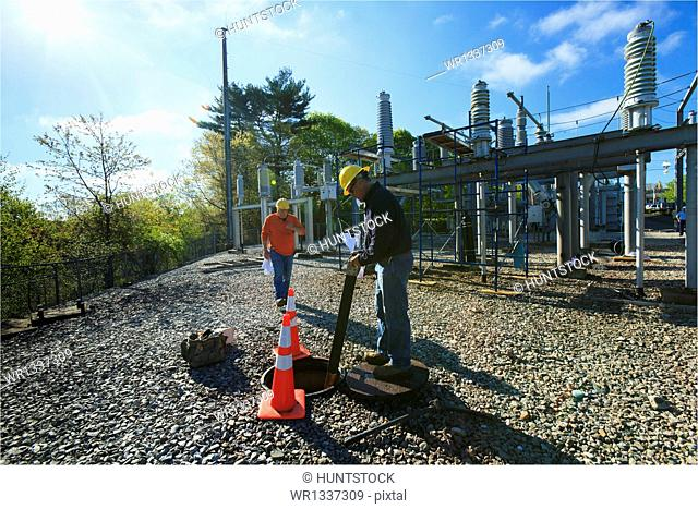 Power engineers working at high voltage power distribution station, Braintree, Massachusetts, USA