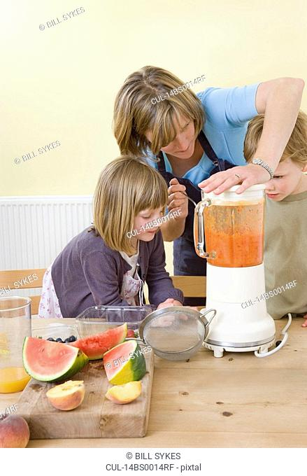 boy, girl and mum making fruit smoothies