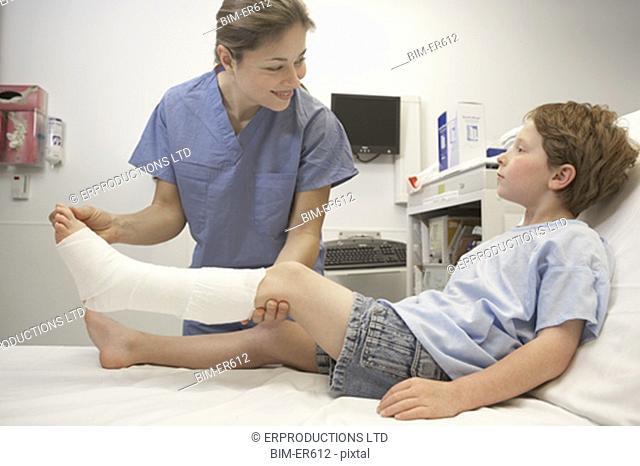 Nurse assisting boy with broken leg