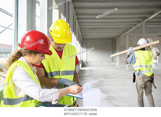 Construction workers with digital tablet and document at building site