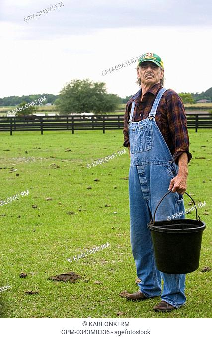 Farmhand in overalls carrying bucket in green pasture