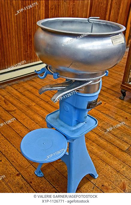 Blue antique cream seperator, sometimes called a creamery which was used to seperator the milk from the cream in past eras Taken inside an old building with...