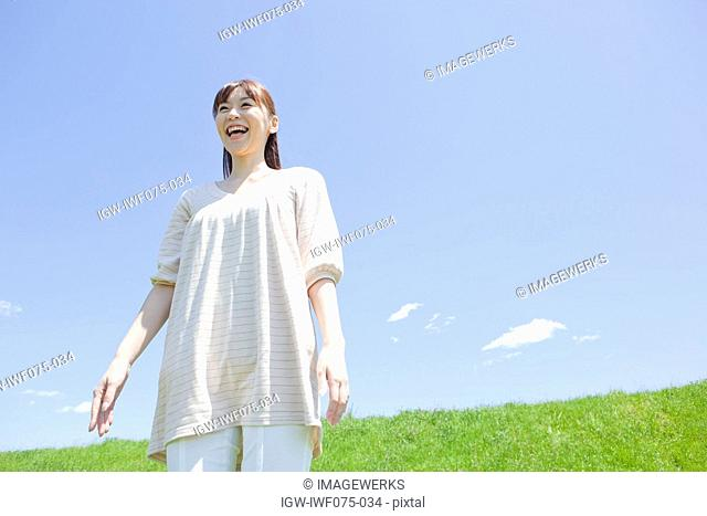 Japan, Tokyo Prefecture, Woman standing in meadow, laughing