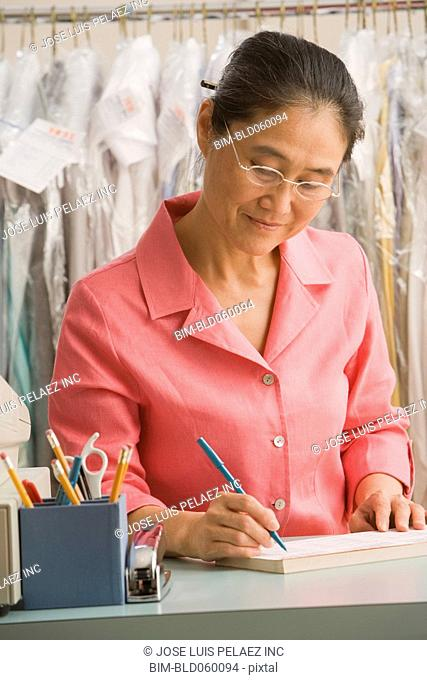 Asian female dry cleaner writing at counter