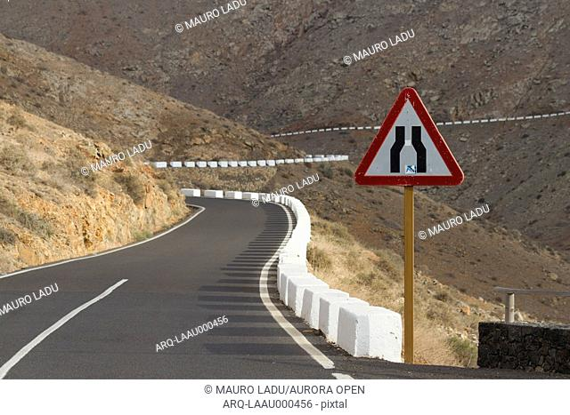 Empty winding road in the middle of a desert and volcanic landscape