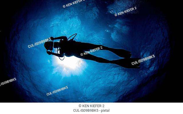 Diver with camera swimming under sunrays