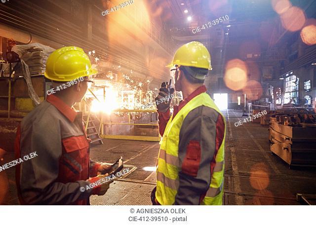 Steelworkers with walkie-talkie watching welding in steel mill