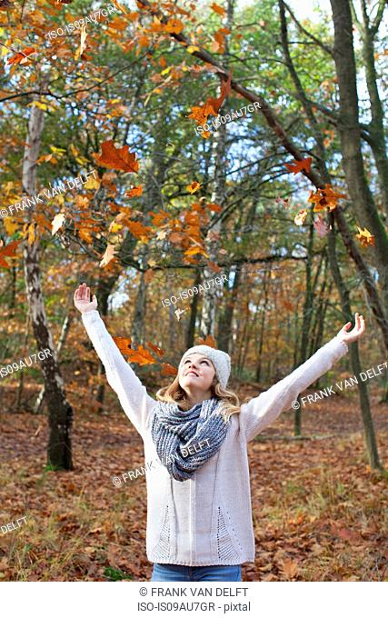 Teenage girl in forest arms raised throwing autumn leaves, looking up smiling