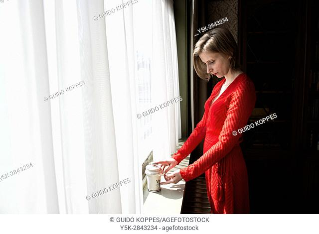 Tilburg, Netherlands. Woman in red dress standing at window still handeling a jar