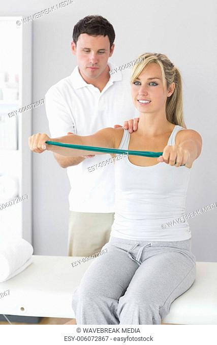 Attractive physiotherapist massaging patient