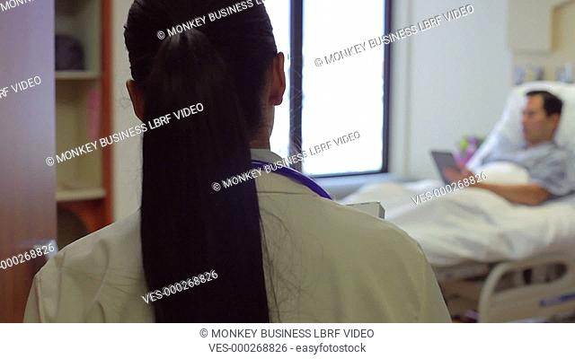 Male patient using digital tablet is visited by female doctor to discuss case.Shot on Sony FS700 in PAL format at a frame rate of 25fps