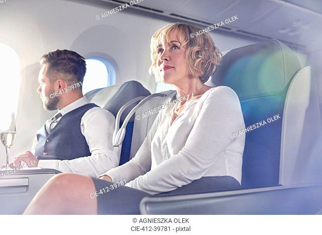 Businesswoman sitting in first class on airplane