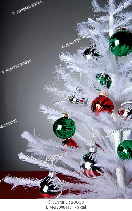 Ornaments on white, artificial Christmas tree