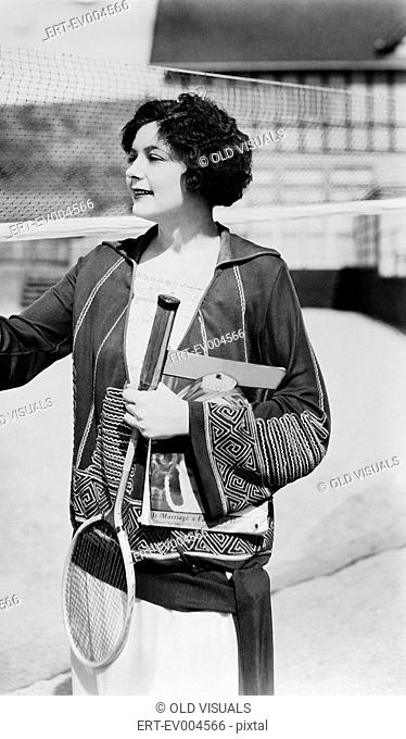 Portrait of woman with badminton racket and magazine All persons depicted are not longer living and no estate exists Supplier warranties that there will be no...