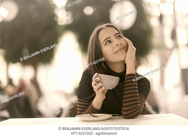 portrait of pleased woman holding coffee cup while enjoying break at table in café, looking to side, in Munich, Germany